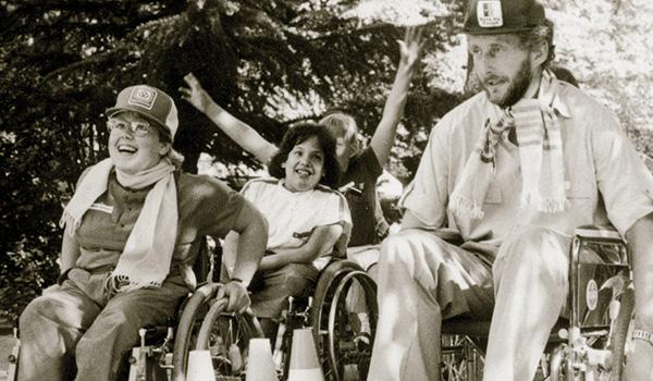 Schwarzweiss Archivfoto, Kinder und ein erwachsener bei einer geschicklichkeits hinterniss- Fahrt in Rollstühlen.