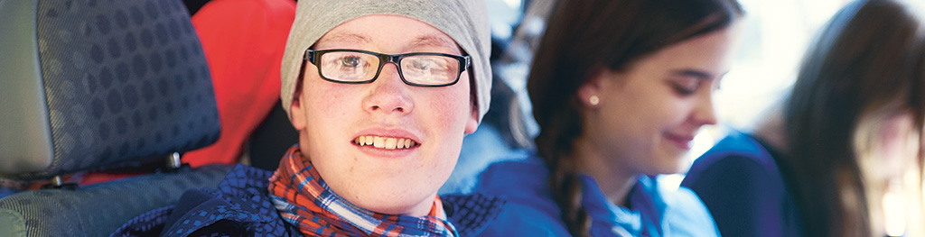 Portrait eines freundlich guckenden Jungen aus einem Autobus heraus. Im Hintergrund unscharf weitere Kinder.