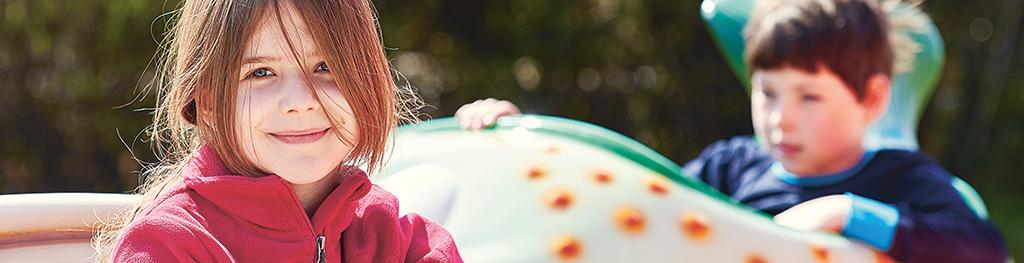 Porträt von einem Mädchen, welches freundlich in die Kamera schaut.