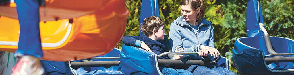Eine Frau und ein Junge blicken sich  im Gespräch an, während sie in einem Karussell sitzen. Die Frau lächelt, die Sonne scheint.