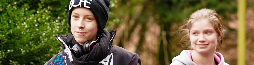 Portrait eines in die Kamera lächelnden Jugendlichen, welcher Nasenring und Lippenpiercing trägt, ein paar Kopfhörer lässig um den Hals hängend.