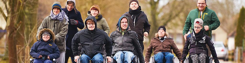 Eine Gruppe jugendlicher Rollstuhlfahrer kommen auf den Betrachter zu, hinter ihnen eine Gruppe Erwachsener laufend. Alle lachen und lächeln.