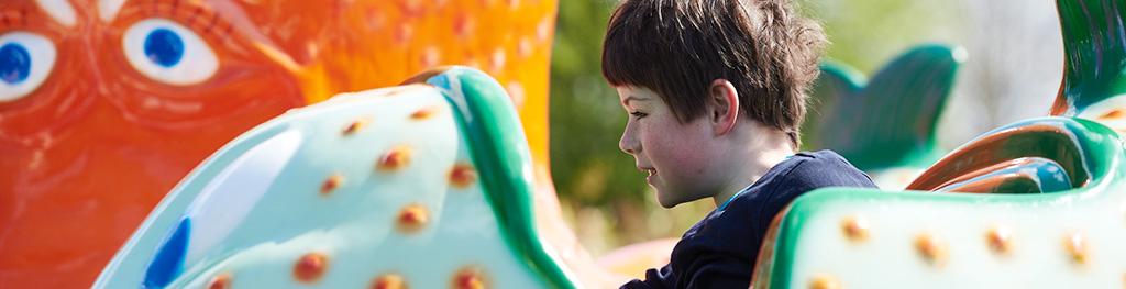 Junge Halbprofil, sitzend in einem Freizeitpark Karussell,Sonnenschein und bunte Farben.