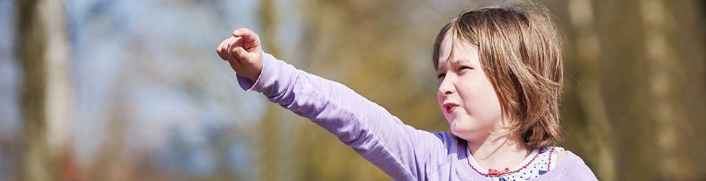 Portrait eines Kindes im Sonnenschein, welches mit dem Finger aus dem Bild heraus deutet.
